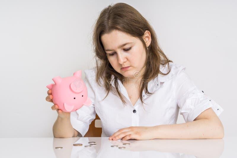 Den unga kvinnan har inga pengar Hennes piggy pengarbank med besparingar är tom arkivbilder