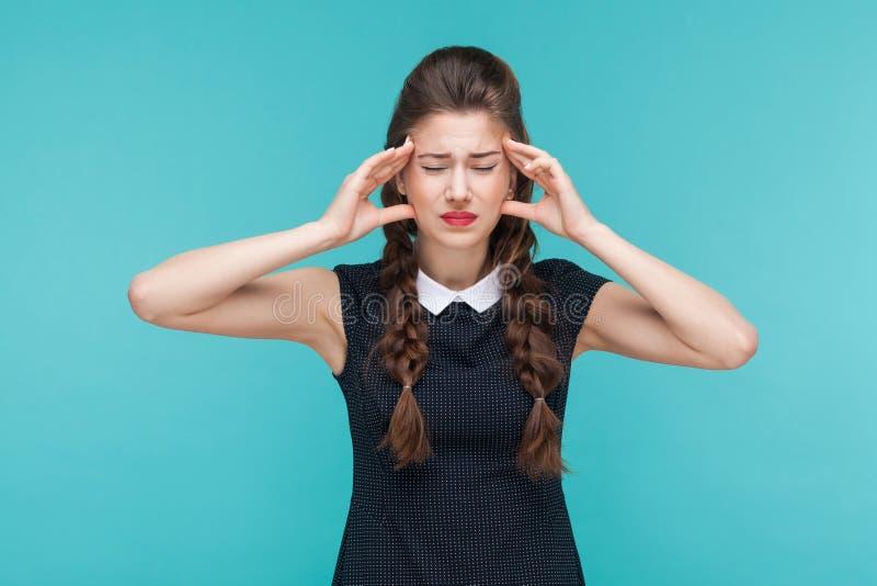Den unga kvinnan har migrän och huvudvärk royaltyfri foto