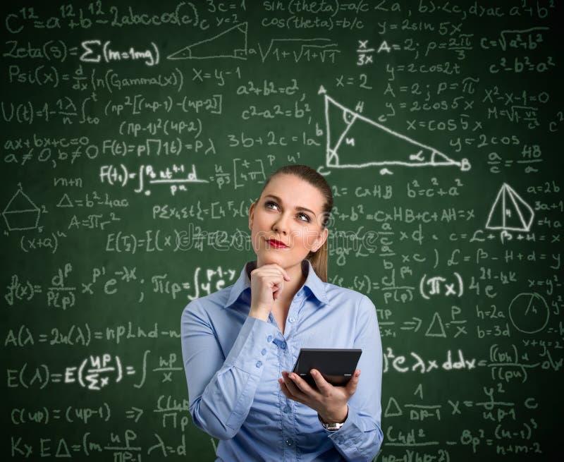 Den unga kvinnan har problem med matematik arkivfoton
