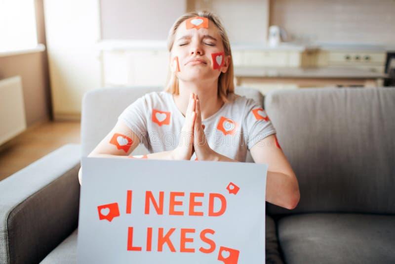 Den unga kvinnan har social massmediab?jelse Addictiveness fr?n smartphones Modellera att tigga för något liknande Instagram liv  royaltyfri fotografi