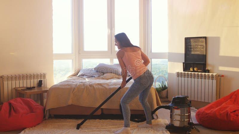 Den unga kvinnan hoovering golvet hemma som använder modern dammsugare och lyssnar till musik med hörlurar, dans arkivbild