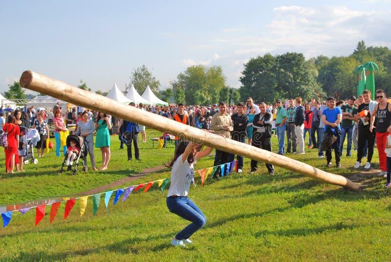 Den unga kvinnan hoppar från en träpinne royaltyfria bilder