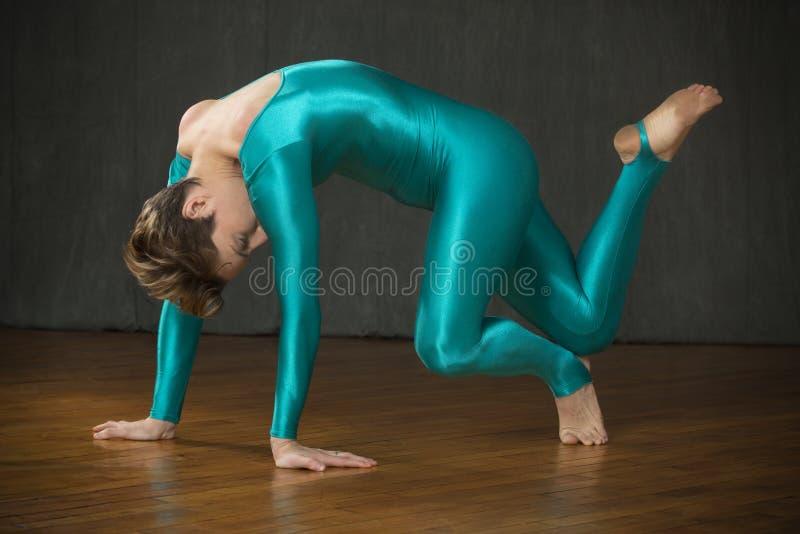 Den unga kvinnan i blått förkroppsligar dräktdans i studion arkivbild