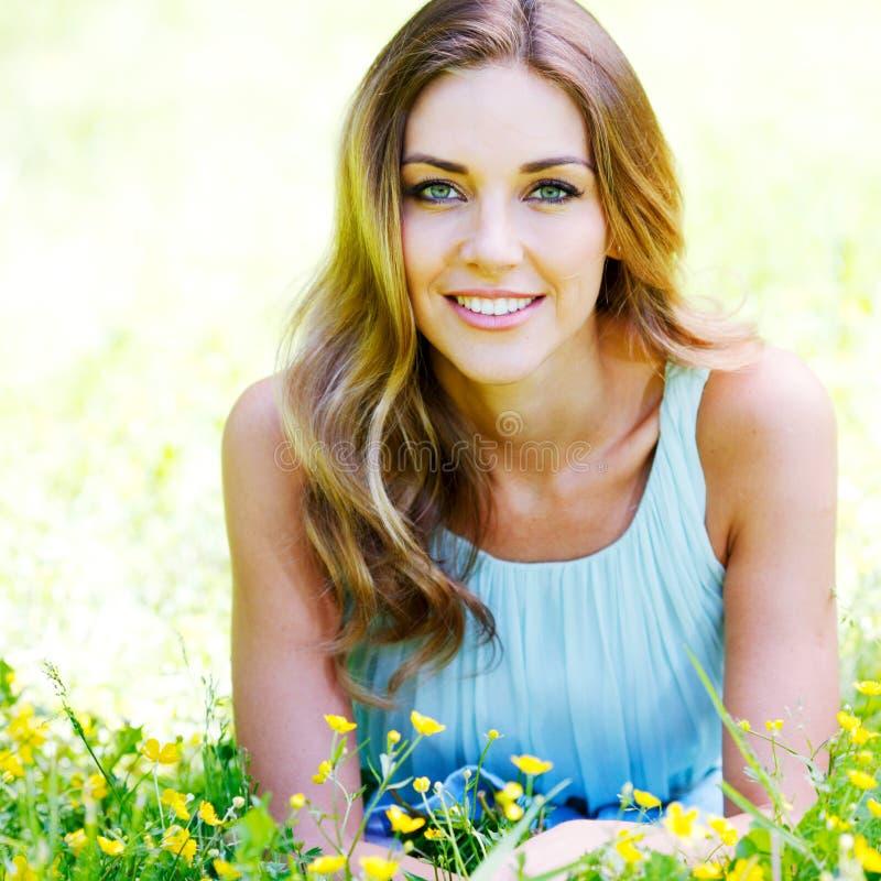 Den unga kvinnan i blått klär att ligga på gräs royaltyfri bild
