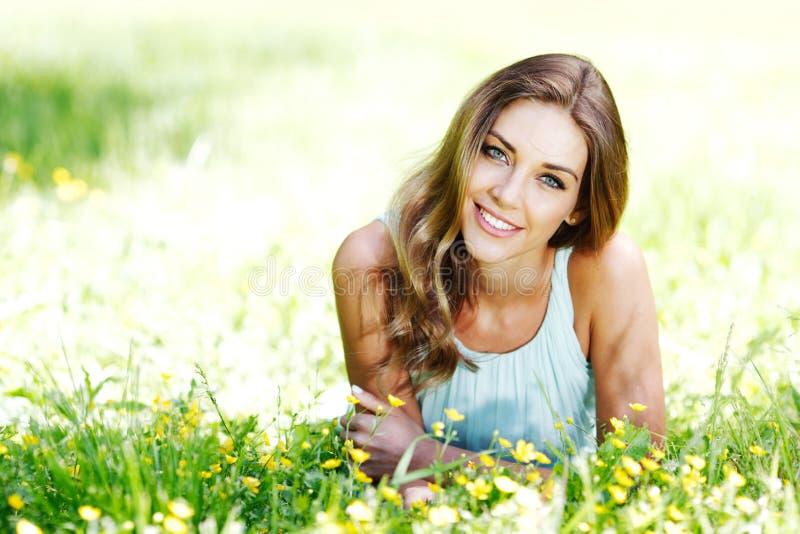 Den unga kvinnan i blått klär att ligga på gräs royaltyfria bilder
