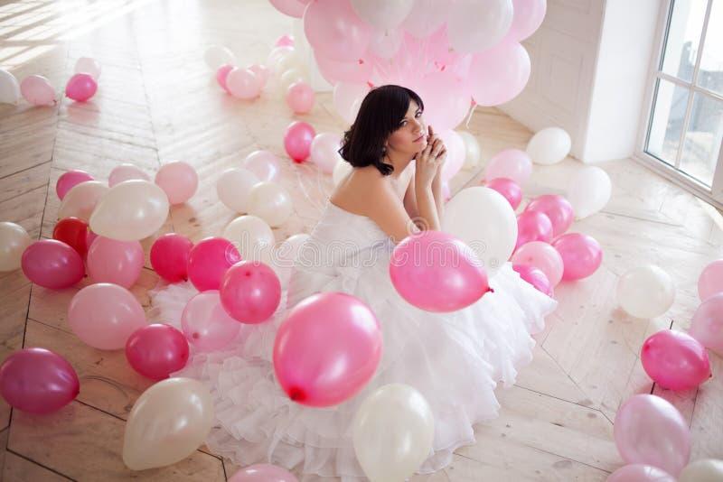 Den unga kvinnan i bröllopsklänning i lyxig inre med en mass av rosa färger och vit sväller arkivbilder