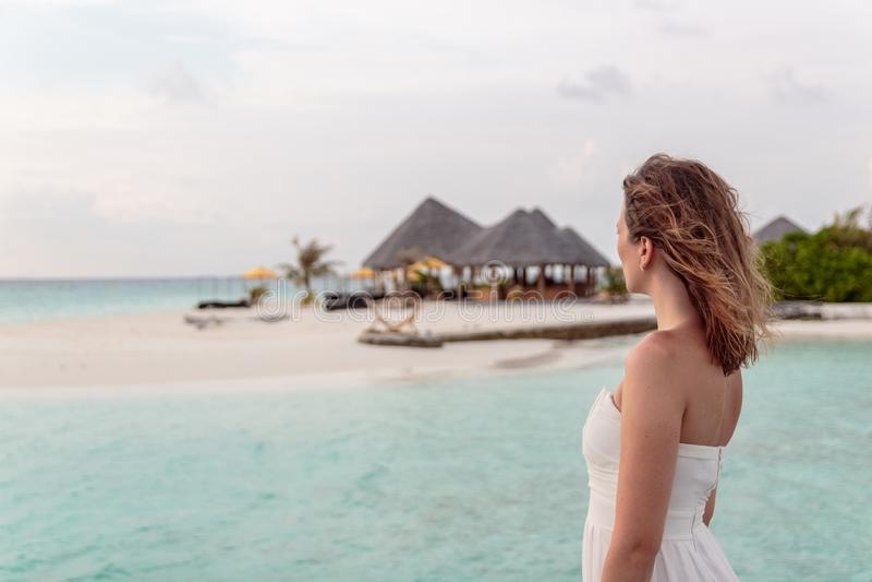 Den unga kvinnan i bröllopsresa kopplar av på en pir som ser solnedgången royaltyfria foton