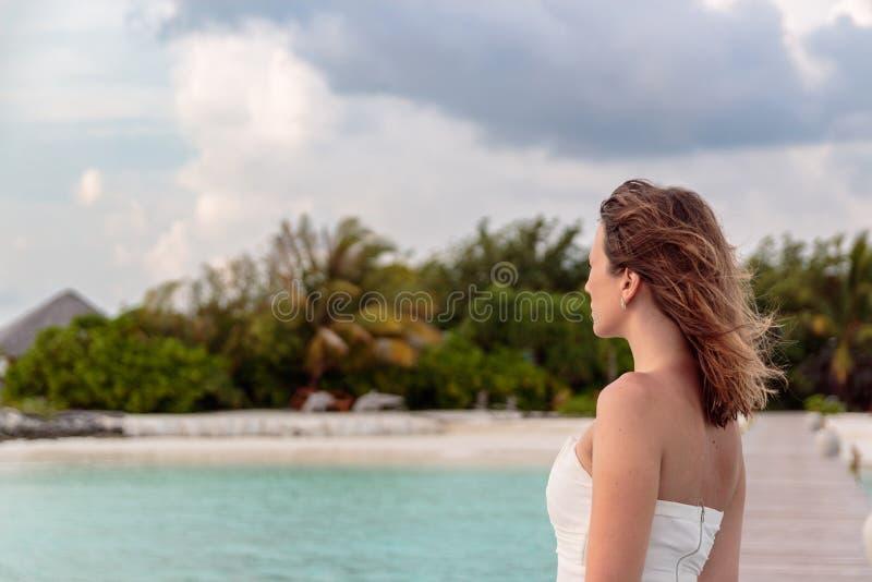Den unga kvinnan i br?llopsresa kopplar av p? en pir som ser solnedg?ngen royaltyfria bilder