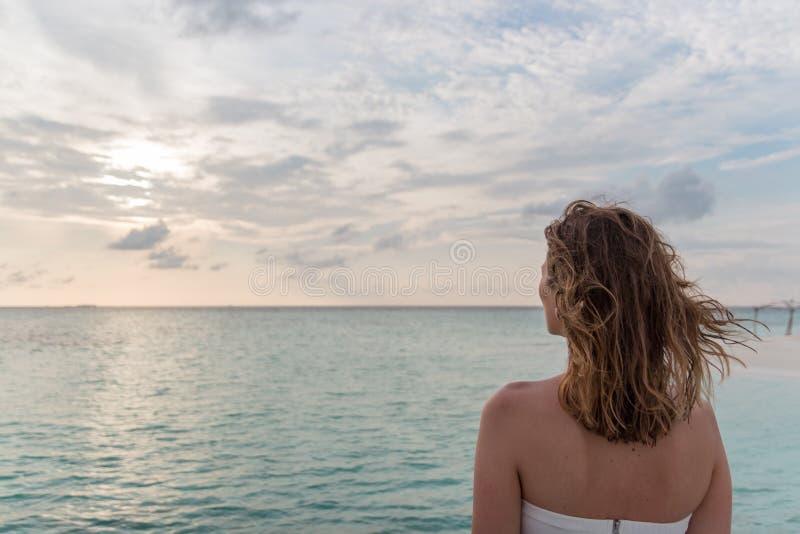 Den unga kvinnan i br?llopsresa kopplar av p? en pir som ser solnedg?ngen arkivfoton