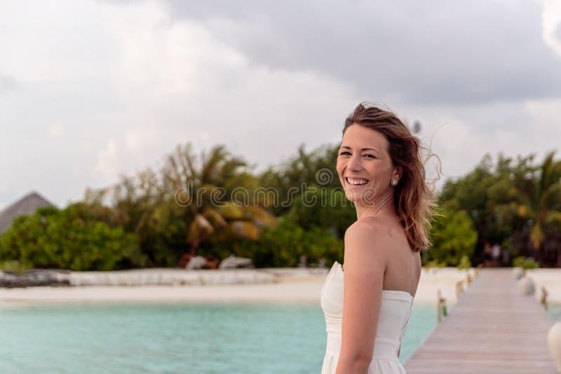 Den unga kvinnan i br?llopsresa kopplar av p? en pir som ser solnedg?ngen royaltyfri fotografi