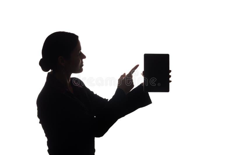 Den unga kvinnan i dr?kt visar pekaren fram?triktat, sidosikten - kontur arkivfoto