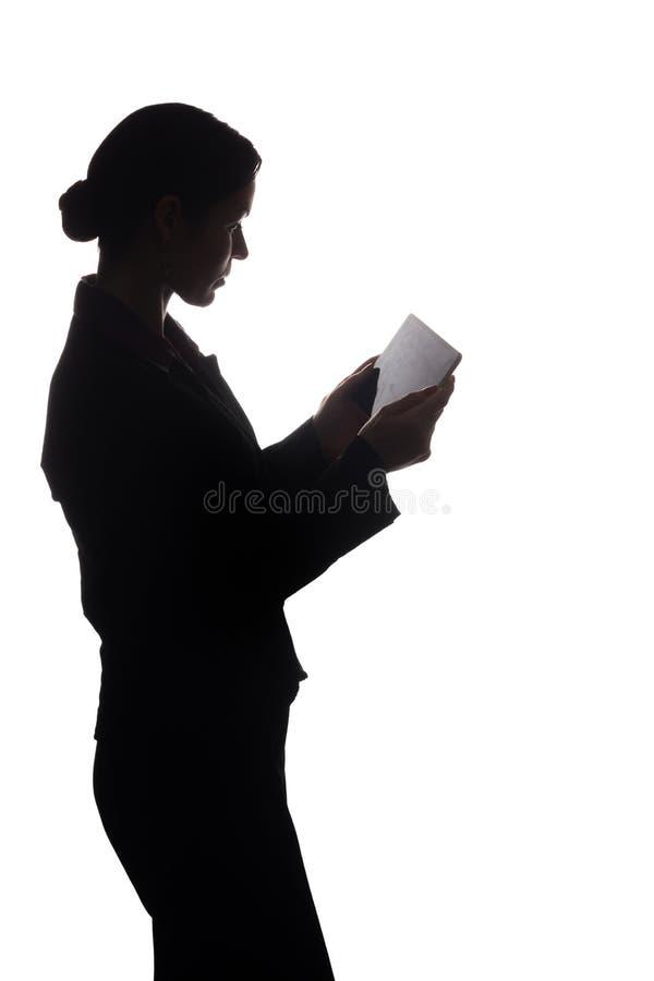 Den unga kvinnan i dr?kt visar pekaren fram?triktat, sidosikten - kontur arkivfoton