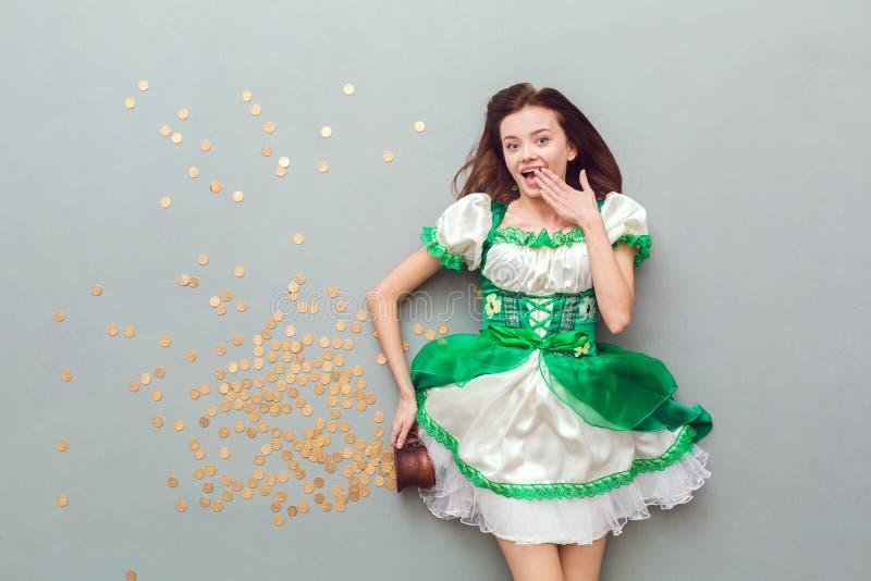 Den unga kvinnan i en bästa sikt för festlig dag för klänningSt Patrick ` s spiller ut mynt royaltyfri bild