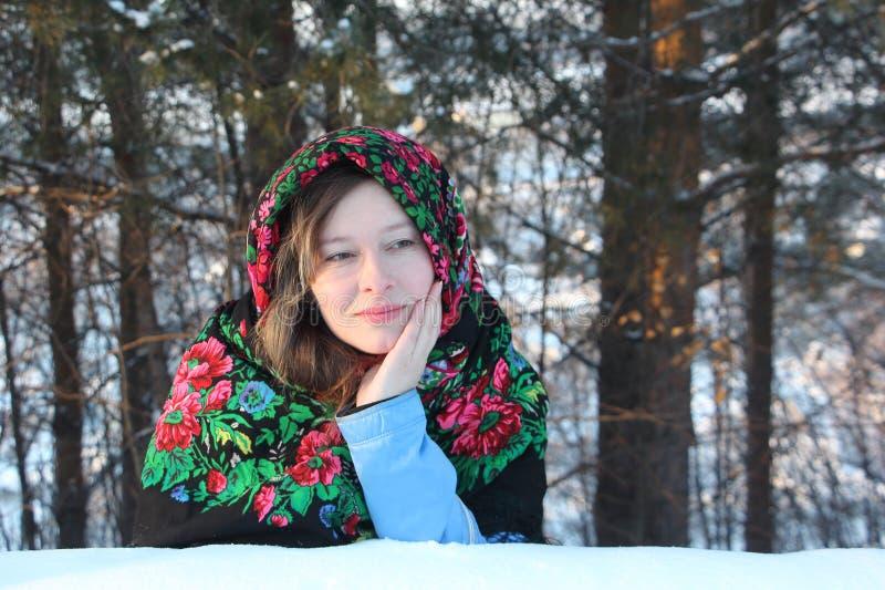 Den unga kvinnan i en elegant woolen halsduk mot trät royaltyfria foton