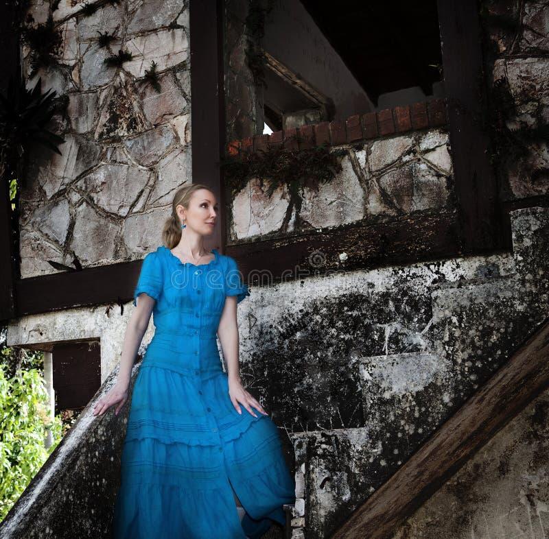 Den unga kvinnan i en lång blått klär ställningar nära den gamla förstörda stenväggen av byggnaden royaltyfria foton