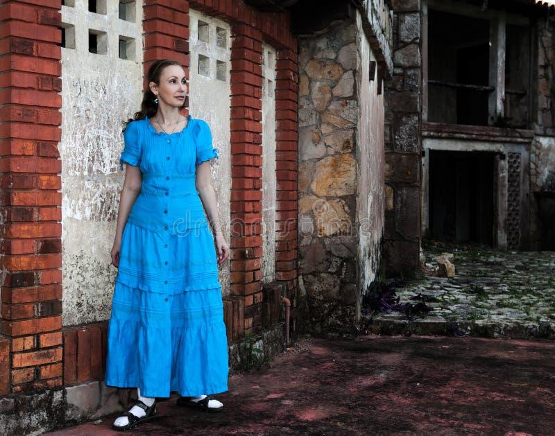 den unga kvinnan i en lång blått klär ställningar nära den gamla förstörda stenväggen av byggnaden royaltyfri fotografi