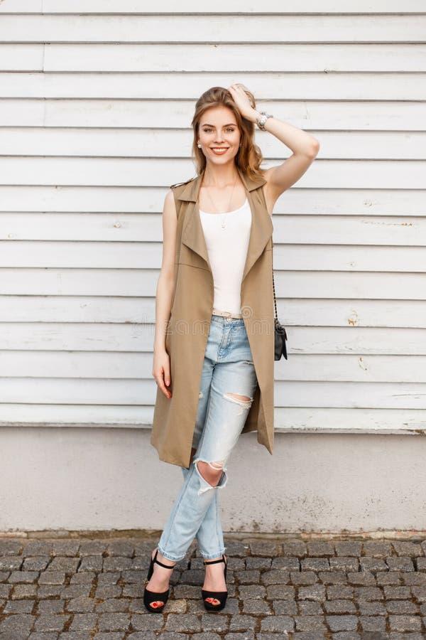 Den unga kvinnan i en stilfull sommar tilldelar en vit T-tröja i trendig blå riven sönder jeans i svarta skor med en läderhandväs arkivfoton