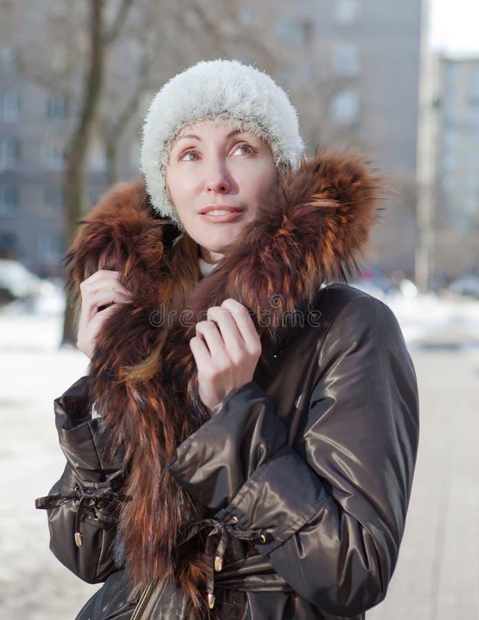Den unga kvinnan i ett omslag med en pälskrage på gatan i vintern. Stående i en solig dag royaltyfria foton