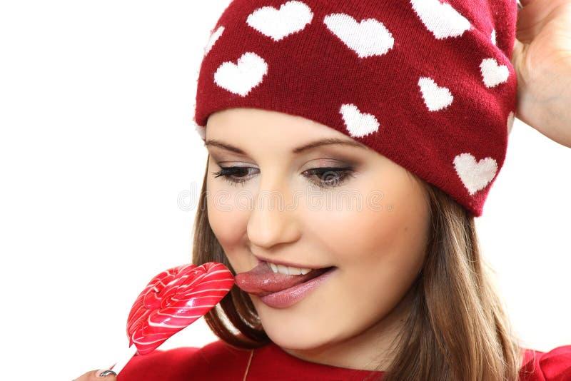 Den unga kvinnan i ett rött lock med hjärtor och med sockergodisen honom royaltyfria bilder