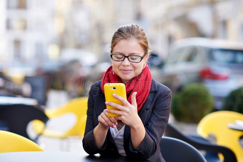 Den unga kvinnan i exponeringsglas skriver sms på telefonen arkivfoto
