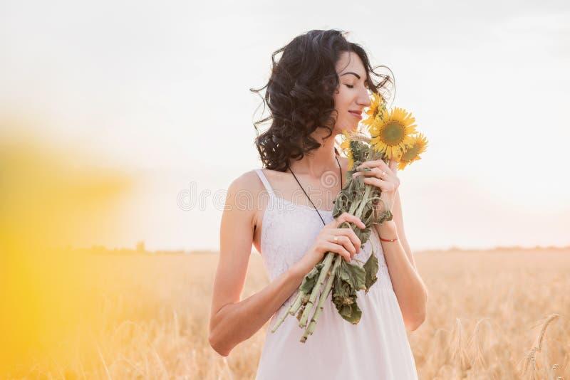 Den unga kvinnan i fältet luktar solrosbuketten royaltyfria foton