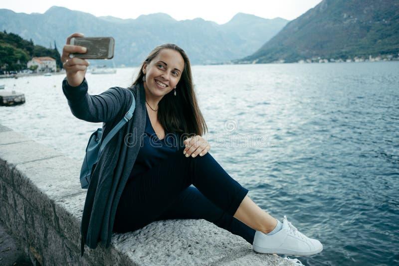 Den unga kvinnan i grå kofta och blåttryggsäck gör selfie på th royaltyfria bilder