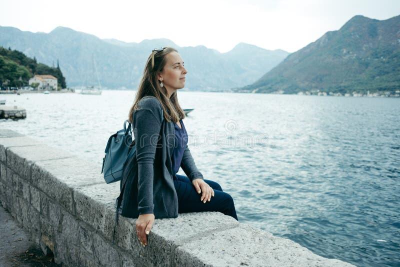 Den unga kvinnan i grå kofta och blåttryggsäck sitter nära havet royaltyfri bild