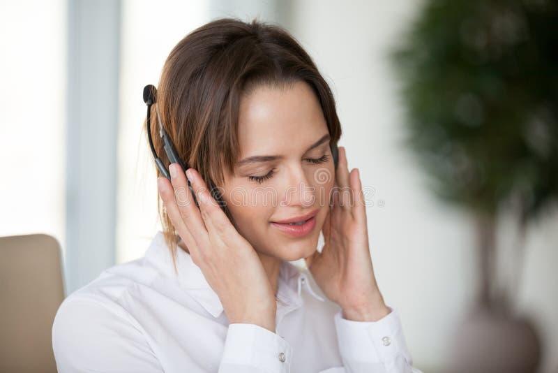 Den unga kvinnan i hörlurar som tycker om angenäm bra musik för, kopplar av royaltyfria foton