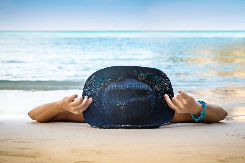 Den unga kvinnan i hatt ligger på den vita sanden på stranden blått hav royaltyfri foto