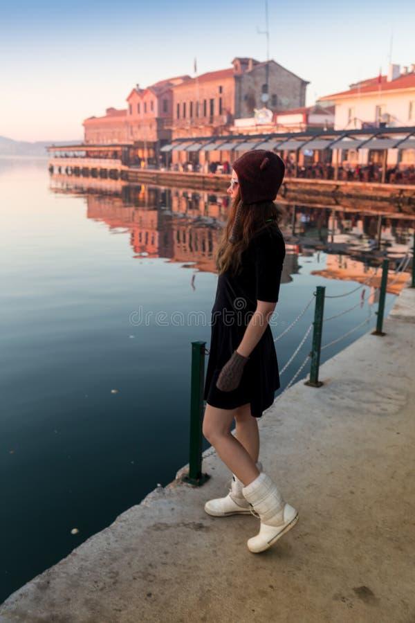 Den unga kvinnan i hatt och gullig sommar klär anseende på pir med fridsamt stadlandskap som ser solnedgång royaltyfri foto