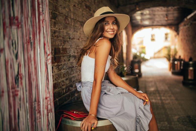 Den unga kvinnan i hatt sitter på stadsgatan bredvid tegelstenväggen av buien arkivbild