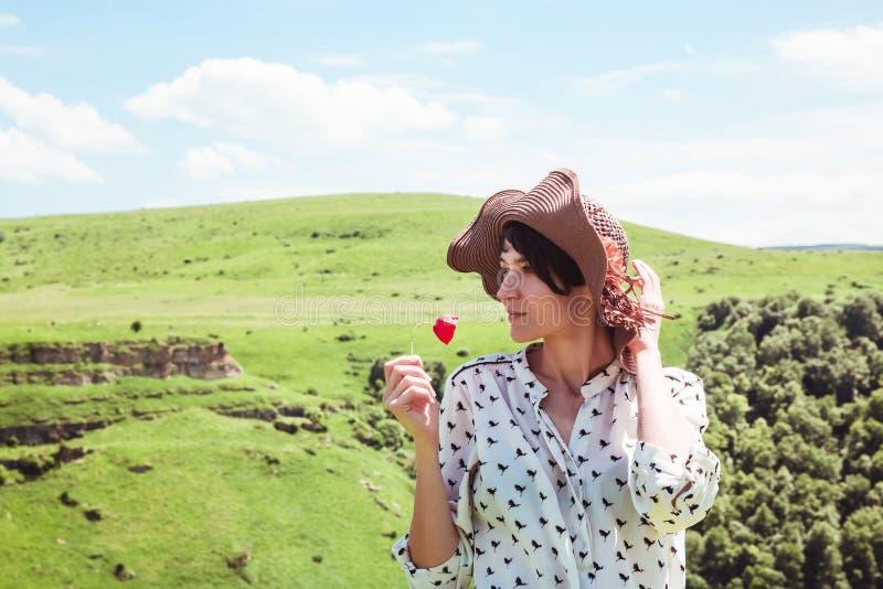 Den unga kvinnan i hatt som tycker om berg, landskap utomhus- aktiv för det röda för blommalopplivsstilen lyckliga för sinnesröre royaltyfri foto
