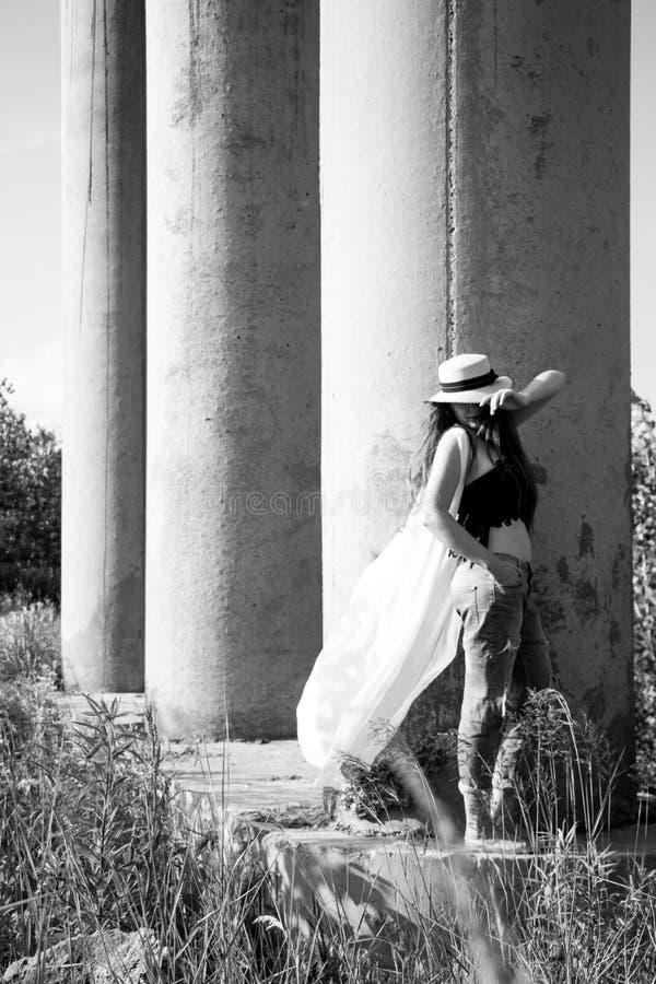 Den unga kvinnan i hatten som går i, parkerar royaltyfri foto