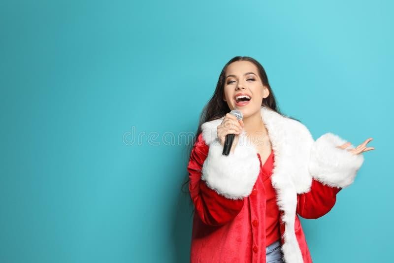 Den unga kvinnan i jultomten kostymerar att sjunga in i mikrofonen på färgbakgrund Julmusik arkivfoto