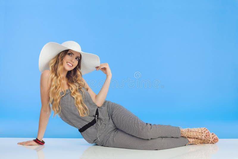 Den unga kvinnan i jumpsuit- och vitsolhatt sitter på golv och ser upp arkivbilder