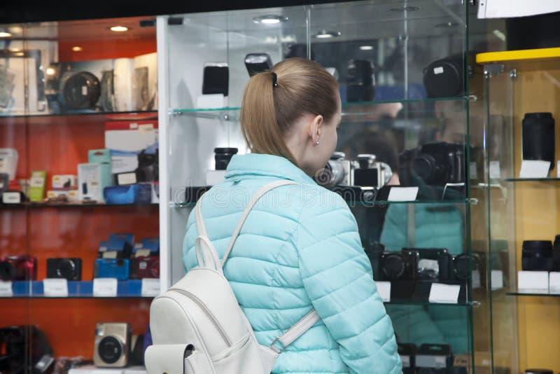 Den unga kvinnan i lager väljer den digitala kameran fotografering för bildbyråer