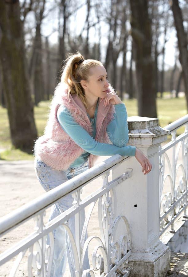 Den unga kvinnan i ljus kläder på bron parkerar in royaltyfria bilder