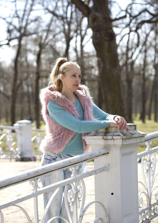 Den unga kvinnan i ljus kläder på bron parkerar in arkivfoto