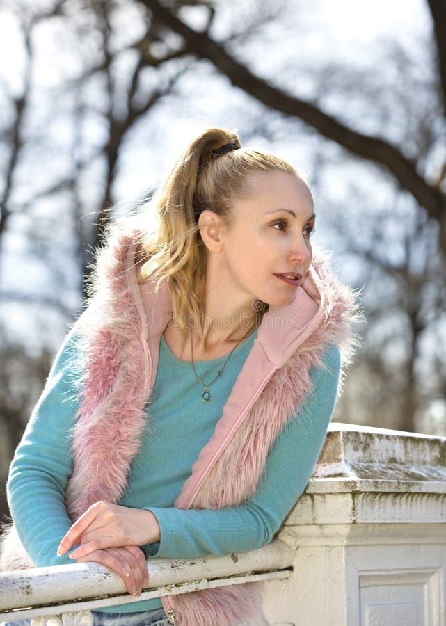 Den unga kvinnan i ljus kläder på bron parkerar in arkivbilder