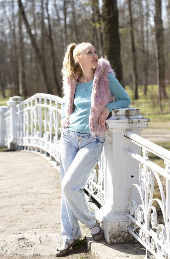 Den unga kvinnan i ljus kläder på bron parkerar in royaltyfri bild