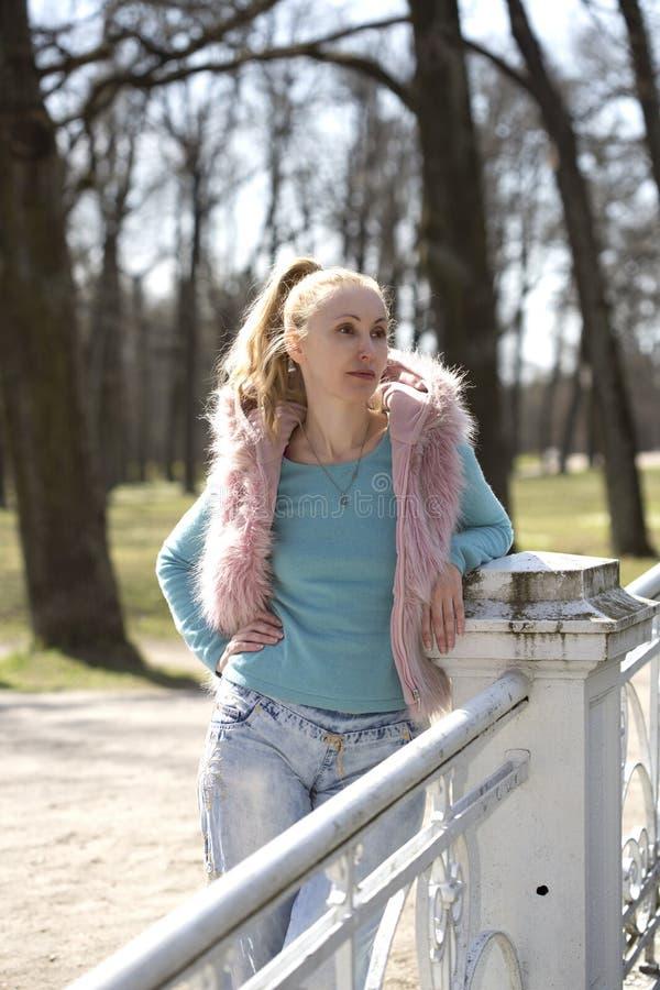 Den unga kvinnan i ljus kläder på bron parkerar in royaltyfri foto