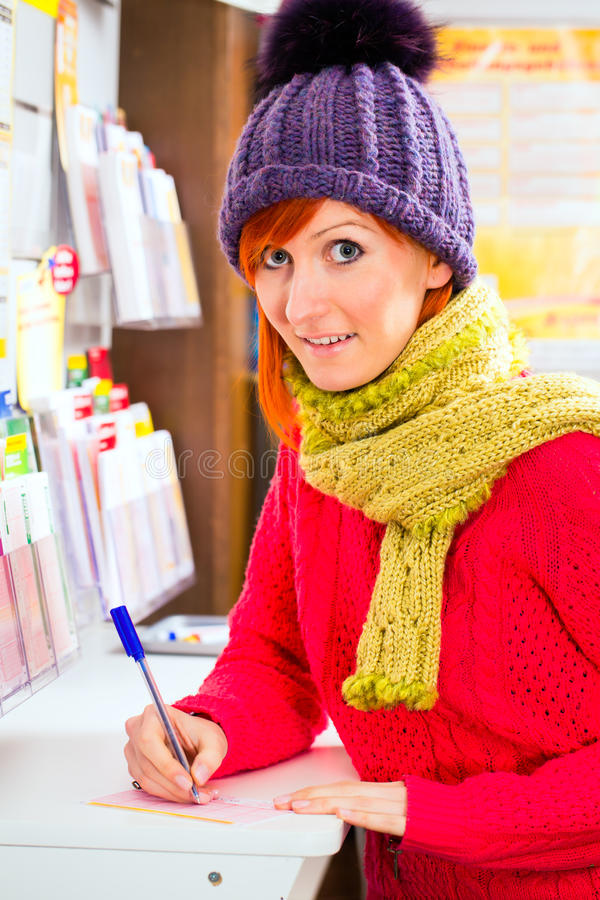 Den unga kvinnan i lotto shoppar spela biljetten royaltyfria bilder