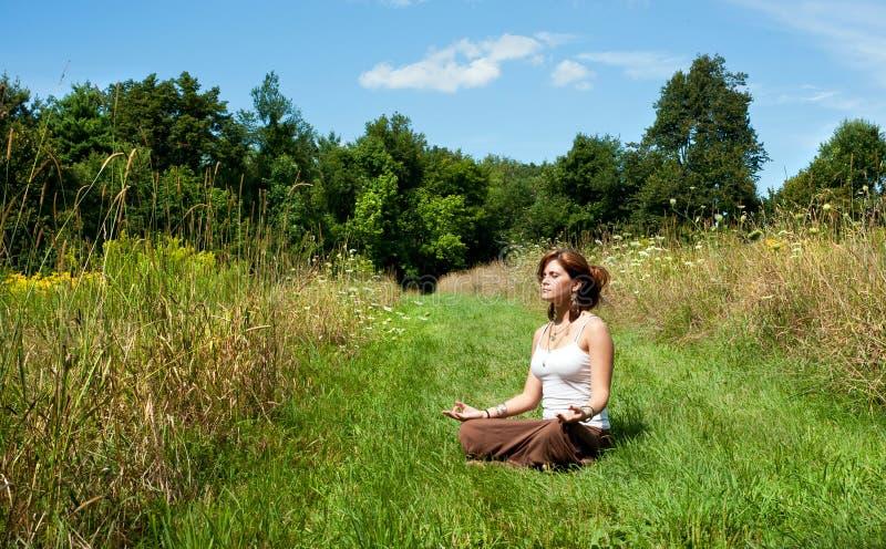 Den unga kvinnan i lotusblomma placerar att meditera arkivfoto