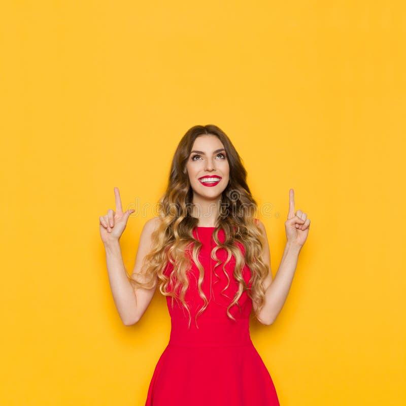 Den unga kvinnan i röd klänning är le, peka och se upp arkivbild