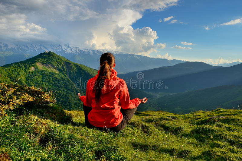 Den unga kvinnan i rött omslagssammanträde i yoga poserar i berg royaltyfria bilder