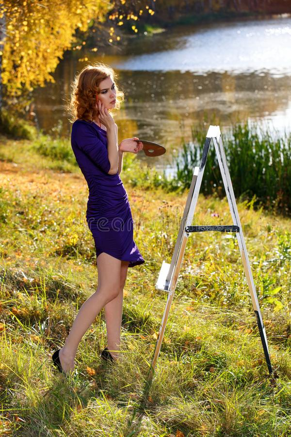 Den unga kvinnan i sexig klänningmålning i höst parkerar utomhus arkivfoton