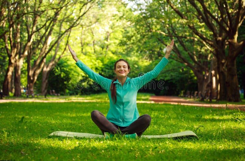 Den unga kvinnan i sommar parkerar att göra yoga med stängda ögon royaltyfri fotografi