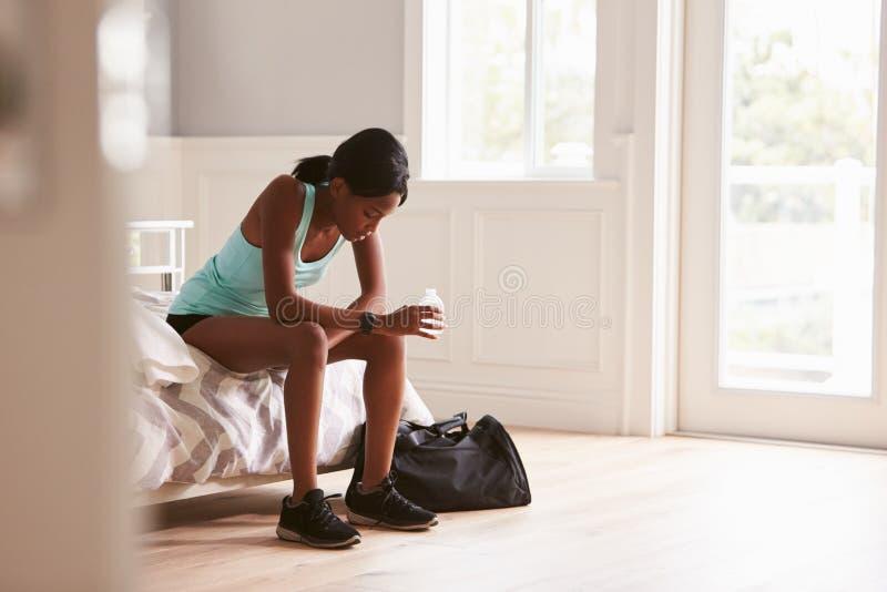 Den unga kvinnan i sportar beklär sittande hemmastatt dricksvatten arkivfoto