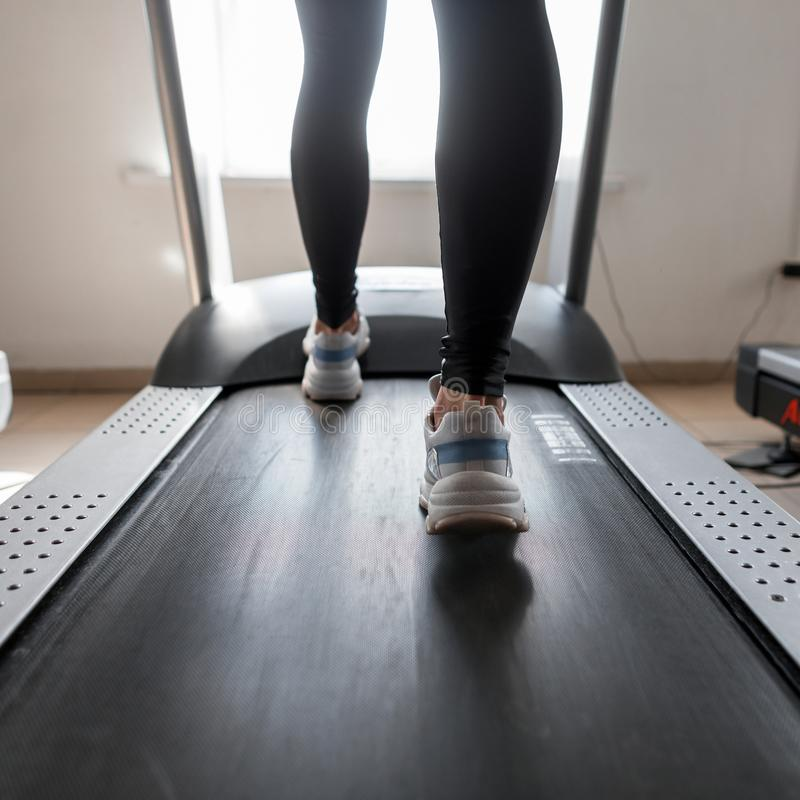 Den unga kvinnan i sportig svart damasker i stilfulla gymnastikskor går på en modern trampkvarn i idrottshallen Flicka som gör ca royaltyfri fotografi