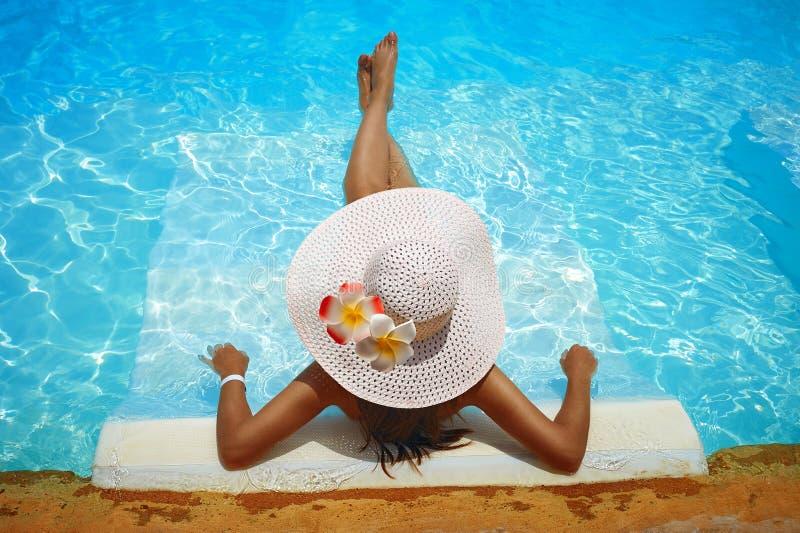 Den unga kvinnan i stor vit hatt vilade på en dagdrivare i pölen royaltyfri fotografi